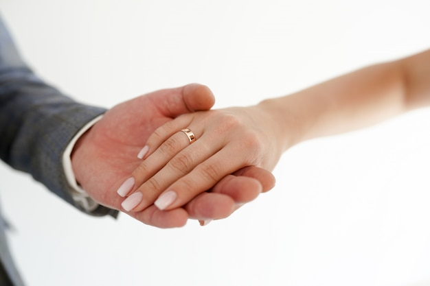 Holding hands with wedding rings on white with copy space.