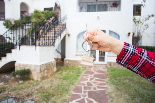 Держа ключи от дома на брелке в форме дома перед новым домом.