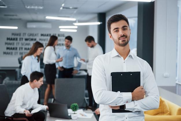 Проведение важных работ. портрет молодого парня стоит в офисе с сотрудниками на фоне