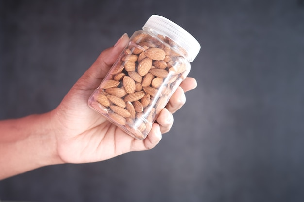 Holding a jar full of almond against black background