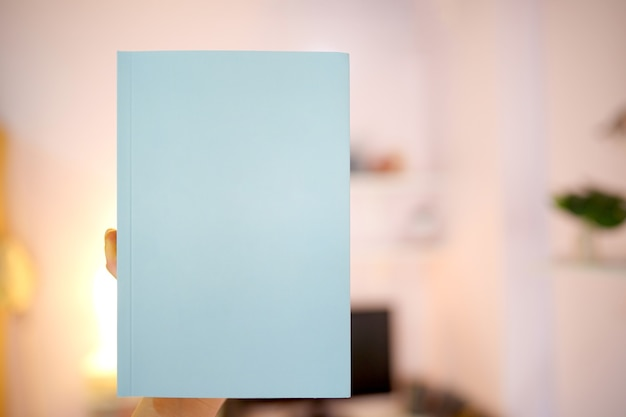 Holding a light blue book with a hand with a blank cover for putting text on a blurry background