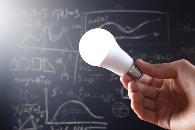 Holding a light bulb on the background of the school board