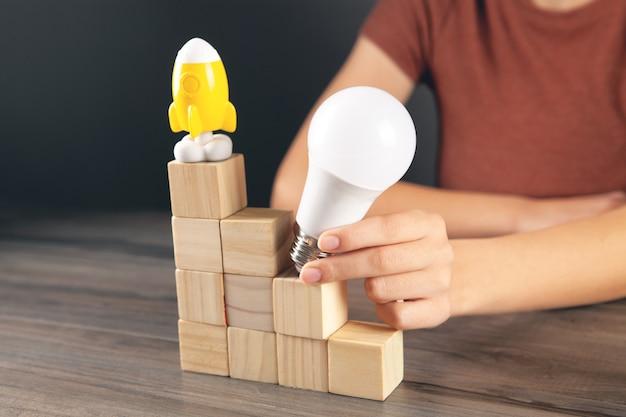 Holding a light bulb a on a ladder made of cubes a rocket