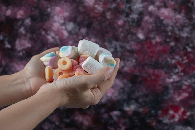 Holding marshmallow and jelly beans mix on hand.