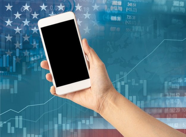 Holding mobile phone to online trade finance global business with usa america flag stock market