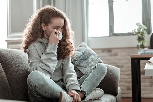 냅킨을 들고. 울고 그녀의 개인적인 문제를 공유하는 동안 냅킨을 들고 곱슬 검은 머리 십 대 소녀
