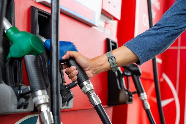 엔진 관리에 연료를 보충하기 위해 노즐 석유를 들고 있습니다. 셀프 서비스 펌프 스테이션. 서비스 자동차 가솔린.