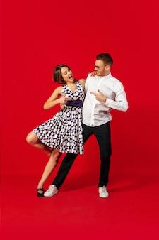 보유. 빨간 스튜디오 배경에서 격리된 구식 젊은 부부 춤. 아티스트 패션, 모션 및 액션 컨셉, 청소년 문화, 패션 복귀. 세련 된 젊은 남자와 여자.