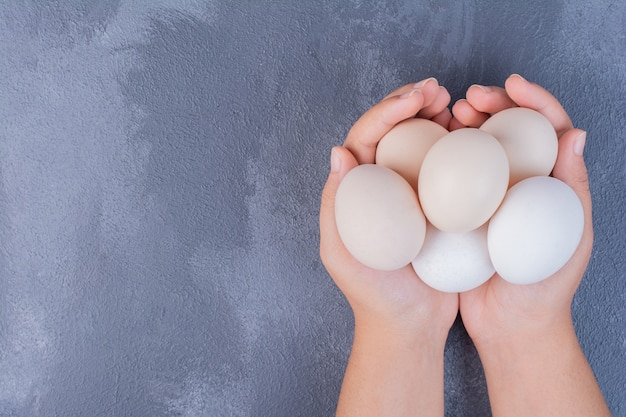 手に有機卵を持っています。
