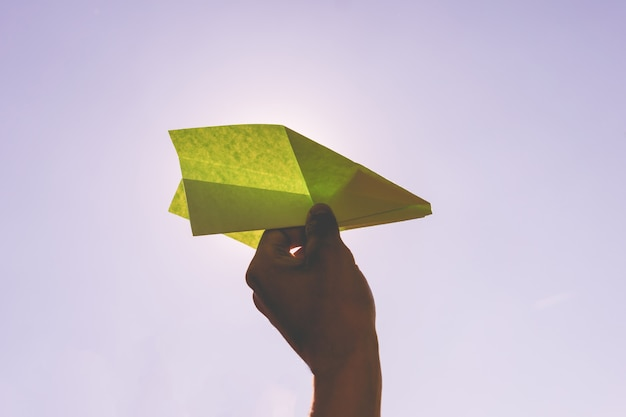 Holding a paper airplane on a summer holiday