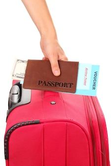 パスポートとスーツケースを手に持ってクローズアップ