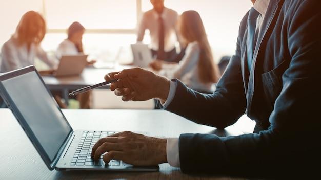 Мужчина-фрилансер держит ручку, указывая на экран компьютера, на котором отображаются сделанные им обновления коллеги. бизнесмен, работающий на ноутбуке в современном офисе. концепция презентации. крупным планом выстрел. тонированное изображение.