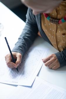 ペンを持っています。テストをチェックしながらペンを保持している素敵なネックレスを身に着けている若い先生