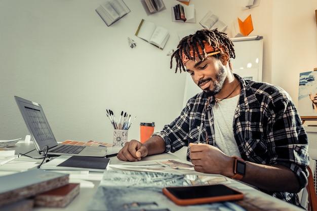 鉛筆を持っています。スケッチを描いている間鉛筆を保持しているドレッドヘアを持つひげを生やした黒髪の芸術家