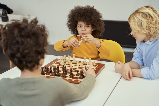 Holding piece awesome little boys discussing game while sitting at the table and playing chess