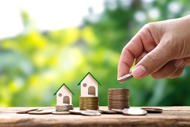 コインの山と家のモデルを保持することはお金の山の上で成長します