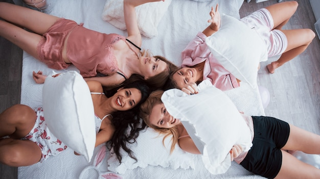 Holding the pillows. top view of young girls at bachelorette party lying on the sofa and raising their hands up