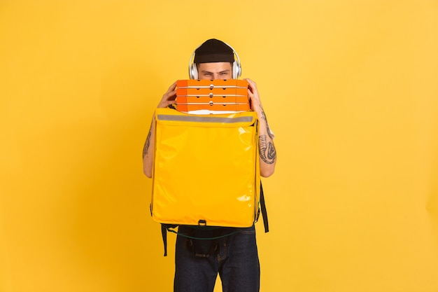 Holding pizza, hiding. emotions of caucasian deliveryman on yellow