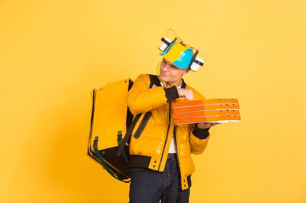 Holding pizza, knocking. emotions of caucasian deliveryman on yellow