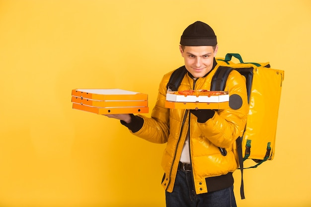 Holding pizzas boxes. emotions of caucasian deliveryman on yellow