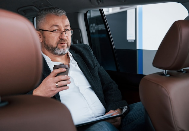 Holding plastic cup of coffee. paperwork on the back seat of the car. senior businessman with documents