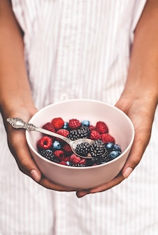 Holding a plate full of berries. breakfast mix. raspberries, blueberries, blackberries. plate