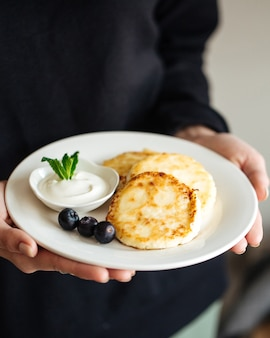 Holding a plate with cottage cheese pancakes