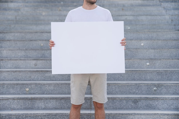 Держит плакат