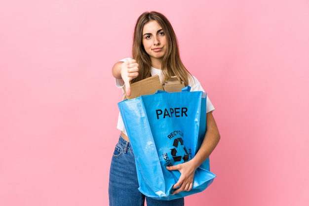 Holding a recycling bag full of paper to recycle over isolated pink showing thumb down sign