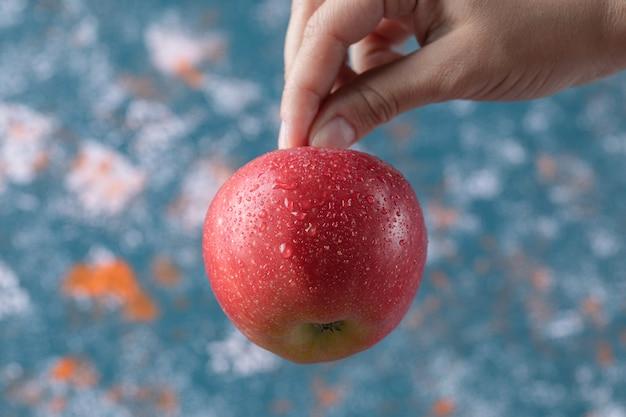 Tenendo una mela rossa dal suo gambo