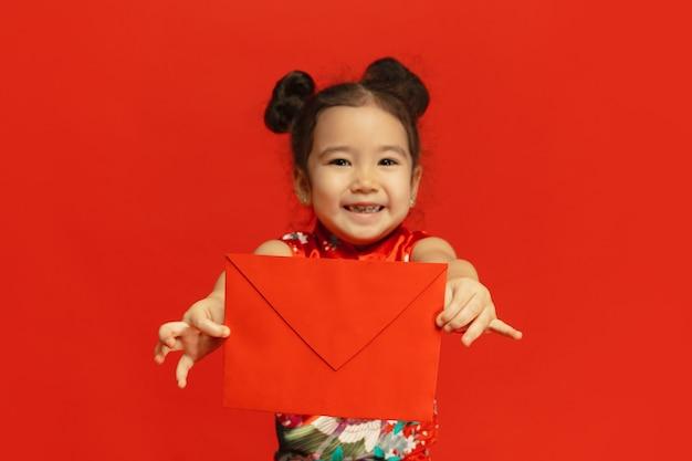 Держит красный конверт, выглядит счастливым, улыбается. счастливый китайский новый год 2020. азиатская милая маленькая девочка изолирована на красном фоне в традиционной одежде. праздник, человеческие эмоции, праздники. copyspace.