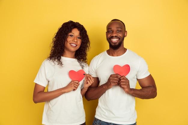 赤いハートを持っています。バレンタインデーのお祝い、黄色のスタジオの背景に分離された幸せなアフリカ系アメリカ人のカップル。人間の感情、顔の表情、愛、関係、ロマンチックな休日の概念。