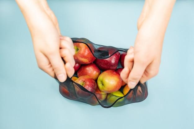 Holding a reusable string bag full of apples.