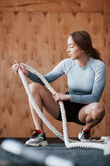 Holding rope for exercises. sportive young woman have fitness day in the gym at morning time
