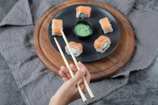 Holding a salmon sushi roll with chopsticks.
