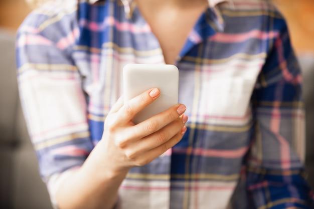 スマートフォンを持っています。オフィスで働いている白人女性の手のクローズアップ。ビジネス、金融、仕事、オンラインショッピングまたは販売の概念。コピースペース。教育、コミュニケーションフリーランス。