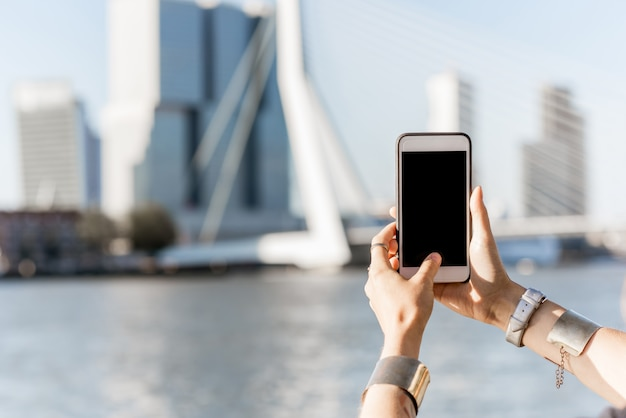 Holding a smartphone with empty screen on the modern cityscape background in rotterdam city