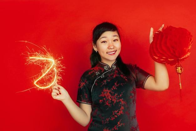 향과 랜턴을 들고. 해피 중국 설날. 빨간색 배경에 아시아 젊은 여자의 초상화. 전통 옷을 입은 여성 모델이 행복해 보입니다. copyspace.