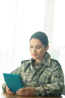 タブレットを保持しています。タブレットを持って遠く離れたまま家族とおしゃべりする女性兵士