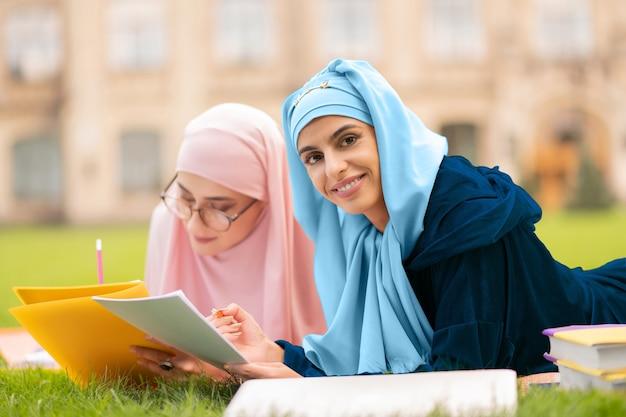 테스트 시트를 들고 있습니다. 친구와 함께 공부하는 동안 테스트 시트와 연필을 들고 hijab를 착용하는 학생의 닫습니다