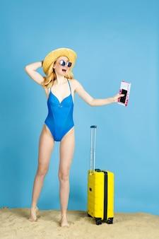 チケットを持っています。青い空間を旅する準備ができてバッグを持つ幸せな若い女性