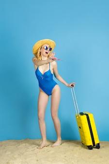 Tenere i biglietti. felice giovane donna con borsa preparata per viaggiare su sfondo blu studio. concetto di emozioni umane, espressione facciale, vacanze estive, fine settimana. estate, mare, oceano, alcol.