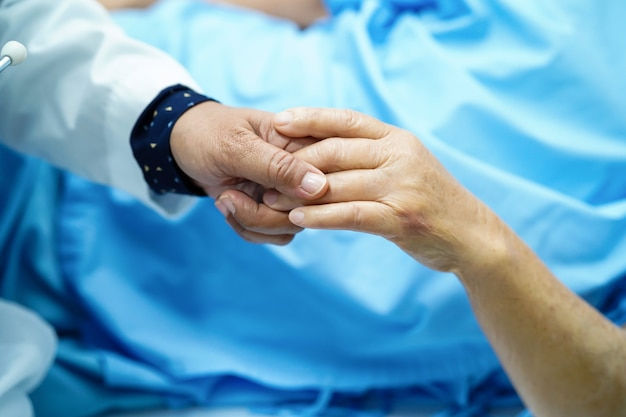 Holding touching hands asian senior or elderly old lady woman patient with love