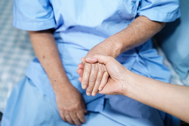 Holding touching hands asian senior or elderly old lady woman patient