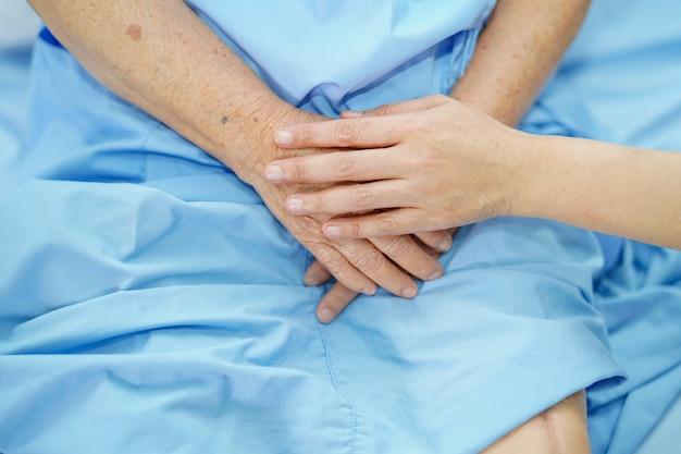 手を触れて手を繋いでいます。アジアの高齢者または高齢者の老婦人女性患者看護師病棟で愛、ケア、援助、励ましと共感:健康的な強い医療の概念