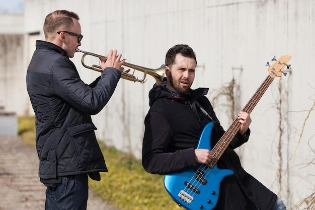 Holding trumpet in friends ear
