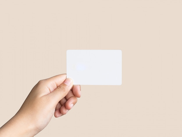 Holding up white business card on pastel color.
