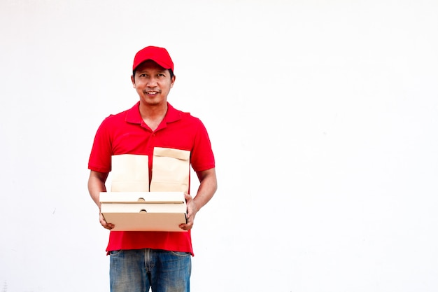 Holding various take-out food containers, pizza box, in holder and paper bag, close-up. light grey background, place to insert your text. delivery man.