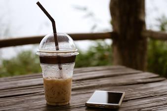 太ももとカフェでコーヒーカップに空白の画面を持つ白い携帯電話を保持