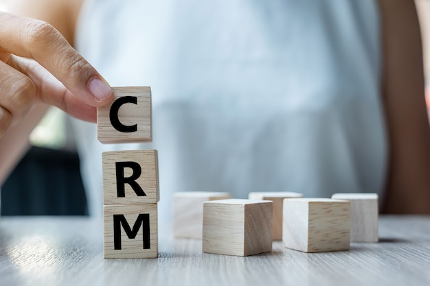 Holding wooden cube with crm text